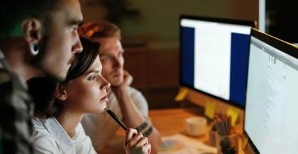 Drei Mitarbeiter*innen einer Software Agentur schauen sich eine SQL Datenbank am Bildschirm an.