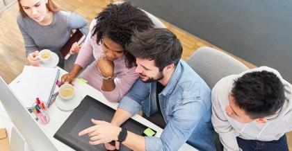Das Team einer Webdesign Agentur in Berlin schaut auf einen Bildschirm und berät über das Webdesign.