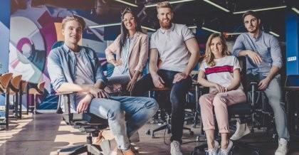 Ein Team einer jungen Softwareagentur in Berlin sitzt auf Stühlen und Tischen und schaut in die Kamera.
