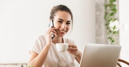 Eine Mitarbeiterin einer Digitalagentur vereinbart telefonisch einen Termin.