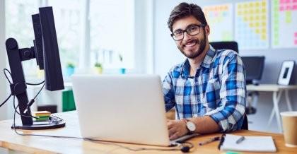 Ein Softwareentwickler sitzt an seinem Arbeitsplatz vor einem Bildschirm und Laptop und programmiert.