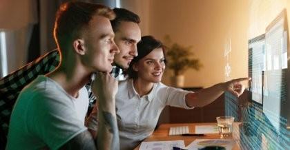 Die Datenbank, über die sich diese Mitarbeiter einer Softwareagentur unterhalten, wird auf einem Bildschirm vor ihnen angezeigt und die Mitarbeiterin zeigt auf den Bildschirm, während die and