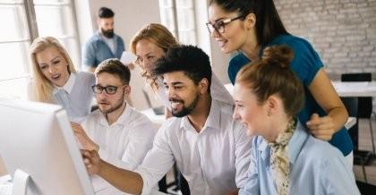 Mitarbeiter*innen schauen auf einen Bildschirm und freuen sich über ihre neue individuell entwickelte Unternehmenssoftware.
