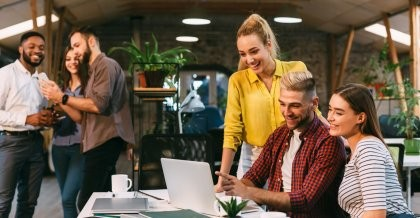 Mitarbeiter*innen einer Software Agentur entwerfen Individualsoftware für Kunden und schauen gemeinsam auf den Bildschirm eines Laptops.