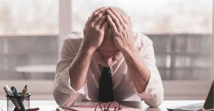Ein Mann schlägt wegen einer schlechten Webseite die Hände über dem Kopf zusammen.
