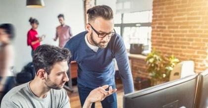 Zwei Mitarbeiter einer Software Agentur schauen auf einen Bildschirm und besprechen den Code der entwickelten individuellen Softwarelösung.
