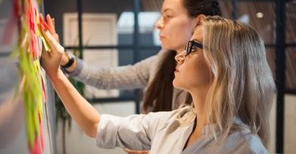 Zwei Mitarbeiterinnen einer Software Agentur arbeiten den Scrum Process bei der agilen Softwareentwicklung aus.