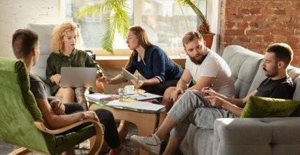 Mitarbeiter*innen eines Unternehmens möchten sich eine Intranetlösung entwickeln lassen und tauschen sich in einer Sitzecke darüber aus.