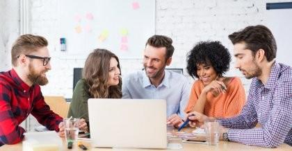Eine Agentur berät über die User Experience für die Entwicklung einer Website im Kundenauftrag am Laptop und nimmt sich kleine Zettel zur Hilfe.