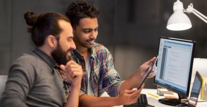 Zwei Mitarbeiter einer Webagentur verwenden eine relationale Datenbank zur Entwicklung einer responsive Website und testen diese auf dem Tablet an ihrem Arbeitsplatz.