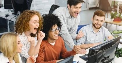 Mitarbeiter*innen einer IT-Agentur schauen auf einen Bildschirm und freuen sich über ihren Erfolg.