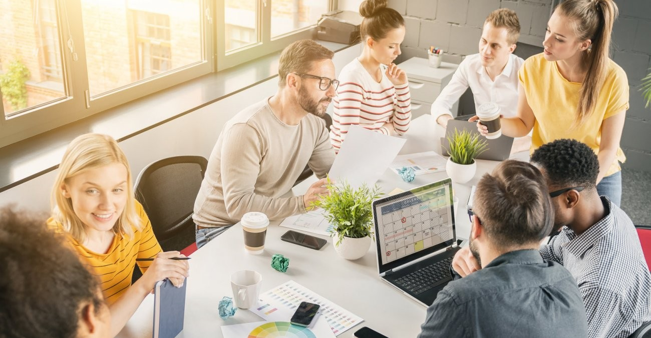 Mitarbeiter eines Unternehmens diskutieren über Individualsoftware oder Standardsoftware als Lösung für ihre Arbeitsprozesse.
