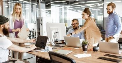 Mitarbeiter*innen eines Unternehmens zeigen auf Bildschirme und tauschen sich über die Unternehmensdatenbank aus.