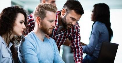 Mitarbeiter*innen einer Agentur arbeiten im Rahmen von IT Outsourcing an einem Kundenprojekt und schauen auf einen Bildschirm.