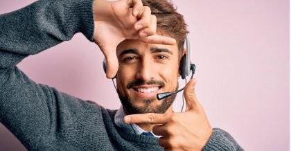 Ein Mitarbeiter eines Call Centers mit Headset freut sich über die bereitgestellte Software.